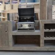 Buitenkeuken met een grill, het keukenblok is gemaakt van steigerhout.