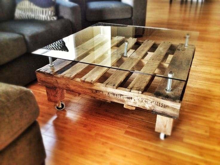 Salontafel met het tafelblad van glas op metalen ondersteuning.