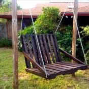 Schommelbank van pallets tussen een frame van rondhout.